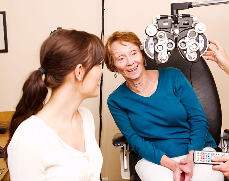 Older lady looking around an eye exam device and smiling